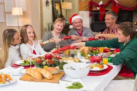 Smiling family pulling christmas crackers at the dinner tableの写真素材 [FYI00004731]