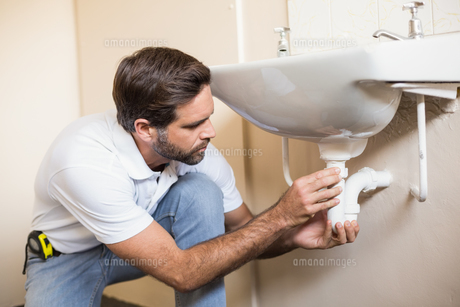 Plumber fixing the sink in a bathroomの写真素材 [FYI00004735]