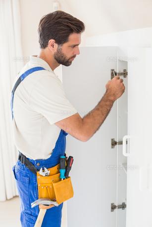 Handyman fixing a wardrobeの写真素材 [FYI00004738]