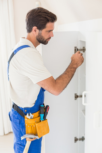 Handyman fixing a wardrobeの写真素材 [FYI00004738]