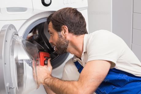 Handyman fixing a washing machineの写真素材 [FYI00004739]