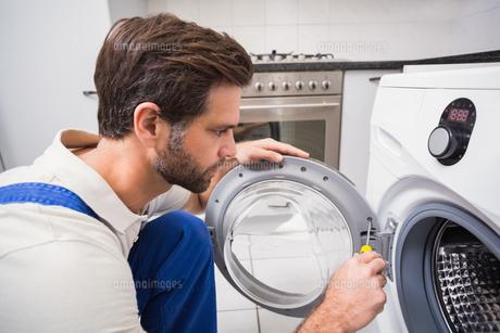 Handyman fixing a washing machineの写真素材 [FYI00004741]