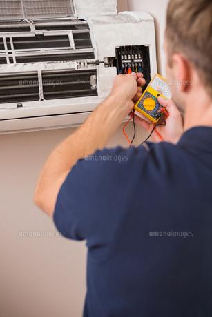 Focused handyman testing air conditioningの写真素材 [FYI00004745]