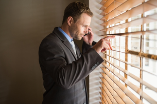 Businessman peeking through blinds while on callの写真素材 [FYI00004751]