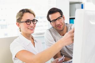 Photo editors looking at computer screenの写真素材 [FYI00004767]