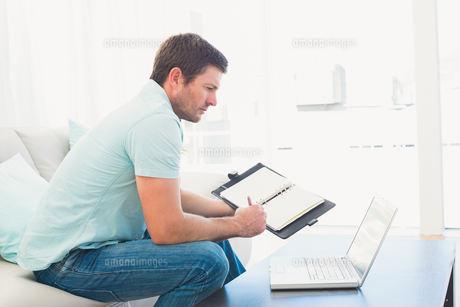 focused man on a laptop with a notebookの写真素材 [FYI00004775]