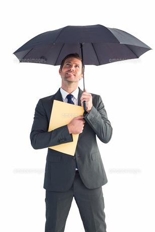 Businessman sheltering under umbrella holding fileの写真素材 [FYI00004779]