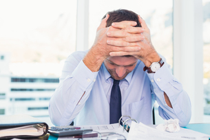 Stressed businessman with head in handsの写真素材 [FYI00004802]