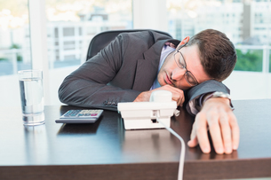 Exhausted businessman sleeping at his deskの写真素材 [FYI00004805]