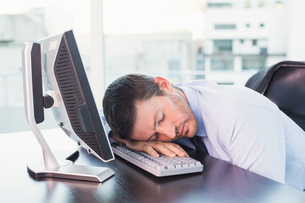 Exhausted businessman sleeping at his deskの写真素材 [FYI00004818]