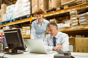 Warehouse management talking and looking at laptopの写真素材 [FYI00004827]