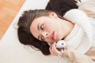 Pretty brunette making a phone call on bedの写真素材 [FYI00004833]