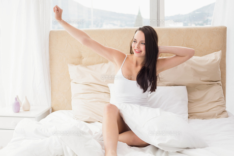 Pretty brunette stretching in bedの写真素材 [FYI00004834]