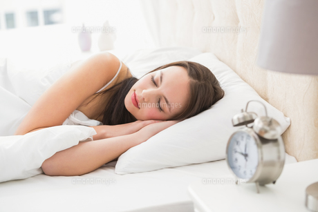 Pretty brunette lying in bed sleepingの写真素材 [FYI00004850]