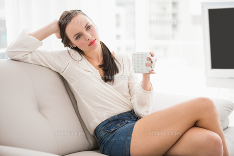 Pretty brunette drinking coffee on the couchの素材 [FYI00004860]
