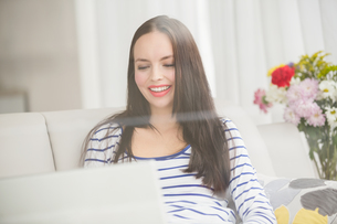 Pretty brunette using laptop on couchの素材 [FYI00004875]