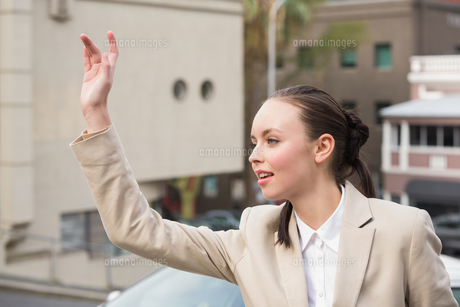 Young businesswoman hailing a cabの素材 [FYI00004882]