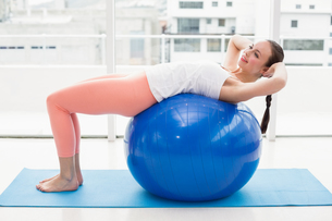 Fit brunette working out with exercise ballの素材 [FYI00004884]