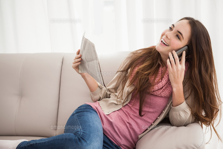 Pretty brunette on the phone holding newspaperの写真素材 [FYI00004904]