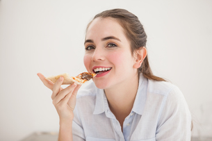 Pretty brunette eating slice of pizzaの写真素材 [FYI00004910]