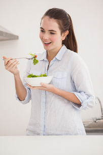 Pretty brunette eating bowl of saladの素材 [FYI00004911]