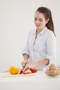 Pretty brunette slicing up peppersの写真素材 [FYI00004917]
