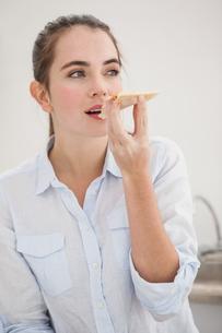 Pretty brunette eating slice of pizzaの写真素材 [FYI00004919]