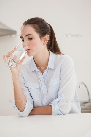 Pretty brunette drinking glass of waterの素材 [FYI00004920]