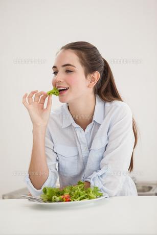 Pretty brunette eating bowl of saladの素材 [FYI00004921]