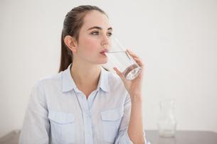 Pretty brunette drinking glass of waterの素材 [FYI00004924]