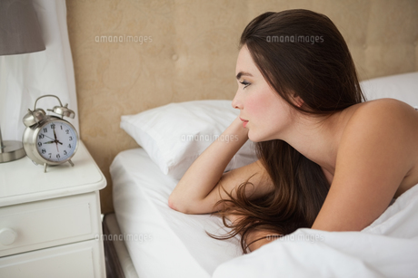Pretty brunette looking at her alarm clockの写真素材 [FYI00004935]