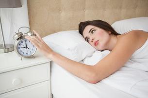 Pretty brunette turning off her alarmの写真素材 [FYI00004936]