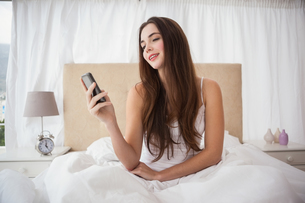 Pretty brunette sending a text in bedの写真素材 [FYI00004937]