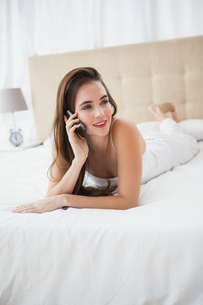 Pretty brunette talking on the phone in bedの写真素材 [FYI00004948]