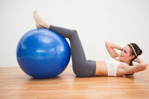 Fit brunette working out with exercise ballの写真素材 [FYI00004957]