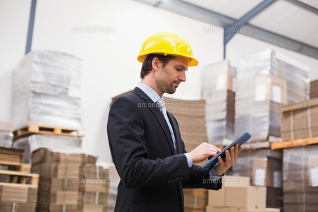 Warehouse manager wearing hard hat using tabletの写真素材 [FYI00004967]