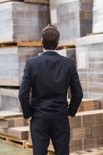 Warehouse manager in suit standing with hands in pocketsの写真素材 [FYI00004968]