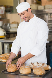 Baker checking freshly baked breadの写真素材 [FYI00004969]