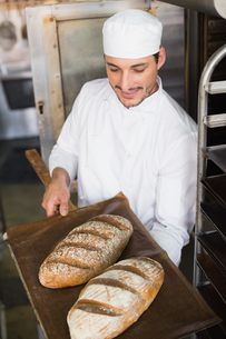 Happy baker holding tray of fresh breadの写真素材 [FYI00004975]