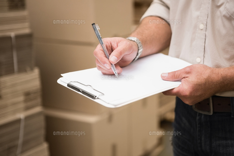 Warehouse worker checking his list on clipboardの写真素材 [FYI00004985]