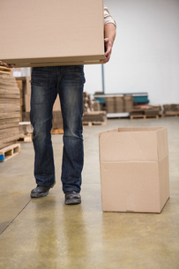 Worker with box in warehouseの写真素材 [FYI00004993]