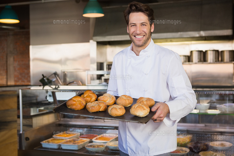Portrait of smiling baker holding tray with breadの写真素材 [FYI00005003]