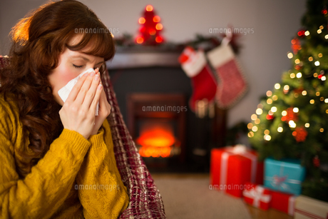 Woman sitting on sofa and blowing her nose at christmasの素材 [FYI00005027]