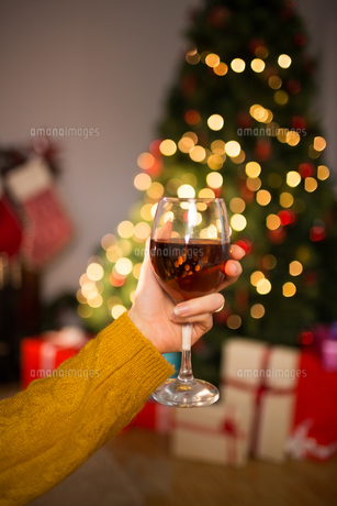 Woman sitting on a couch while holding a glass of red wineの素材 [FYI00005028]