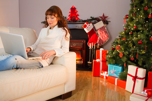Smiling redhead woman using laptop on couch at christmasの写真素材 [FYI00005029]