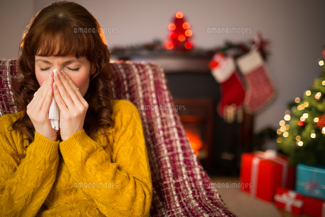 Woman sitting on sofa and blowing her nose at christmasの素材 [FYI00005030]