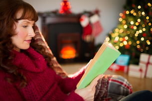 Beautiful redhead reading on the couch at christmasの写真素材 [FYI00005031]