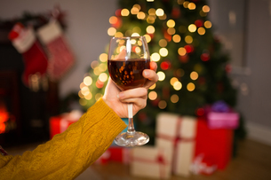 Woman sitting on a couch while holding a glass of red wineの素材 [FYI00005036]