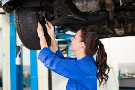 Smiling mechanic adjusting the tireの写真素材 [FYI00005041]