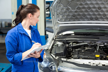 Mechanic writing on clipboard looking at carの写真素材 [FYI00005042]